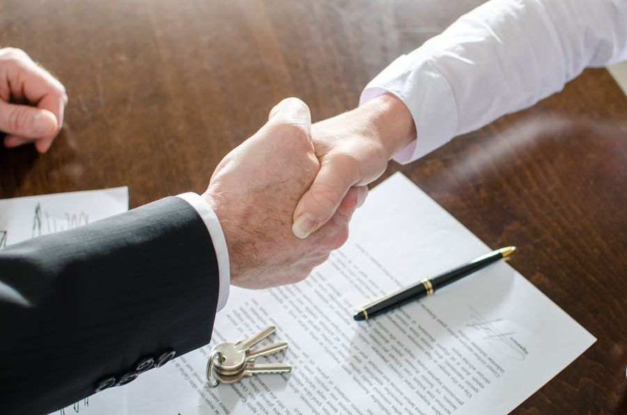 Estate agent shaking hands with his customer after contract signature